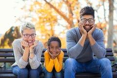 花费与他们的女儿的年轻混合的族种夫妇时间 库存图片