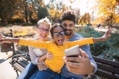 花费与他们的女儿的年轻混合的族种夫妇时间 免版税库存图片