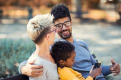 花费与他们的女儿的年轻混合的族种夫妇时间 免版税图库摄影