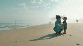 花费与她美丽的矮小的儿子的年轻俏丽的母亲时间在早晨海滩上大西洋 股票录像