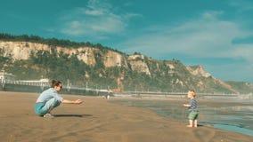 花费与她美丽的矮小的儿子的年轻俏丽的母亲时间在早晨海滩上大西洋 影视素材