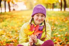 花费与秋叶的时间的十几岁的女孩 秋叶的女孩在新鲜空气的公园 库存图片