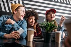花费在咖啡馆的小组年轻朋友时间 库存图片