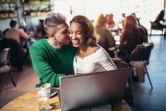 花费在咖啡馆观看的媒介的年轻人种间恋人时间在膝上型计算机上 免版税库存照片