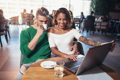 花费在咖啡馆观看的媒介的年轻夫妇时间对膝上型计算机 库存图片