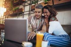 花费在咖啡馆观看的媒介的恋人时间在膝上型计算机上 图库摄影
