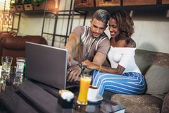 花费在咖啡馆观看的媒介的恋人时间在膝上型计算机上 库存图片