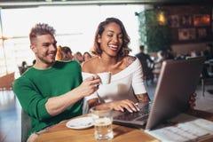 花费在咖啡馆观看的膝上型计算机的年轻夫妇恋人时间 图库摄影