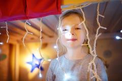 花费她的时间的逗人喜爱的小女孩在装饰的孩子屋子里的圣诞节 在背景的五颜六色的光 美妙的Xmas时间 免版税库存照片