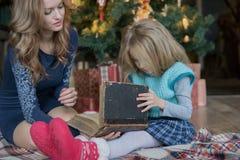 花费悠闲时间读书的妈妈和女儿在圣诞树 免版税图库摄影