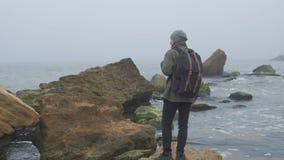 花费时间的后面观点的一个孤独的成人人通过去和看在狂放的海边区域的秀丽图片上 股票录像