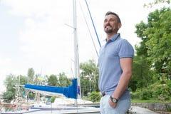 花费时间的商人走在小游艇船坞上和注视着观光假期 年轻愉快的驾游艇者画象  库存图片
