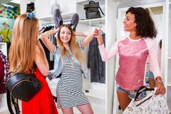 花费时间的小组女朋友一起获得做购物的乐趣 显示有鞋子的俏丽的女孩耳朵以时尚 免版税图库摄影