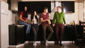 花费时间的年轻可爱的朋友公司一起站立在厨房上 谈,笑和吃快餐 股票录像