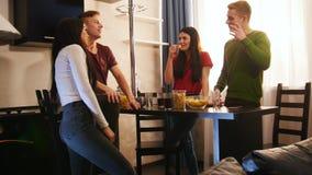 花费时间的年轻朋友公司一起站立在厨房上,吃芯片和谈话 股票视频