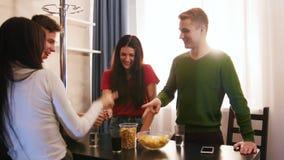 花费时间的年轻朋友公司一起站立在厨房上 演奏岩石纸剪刀 股票录像