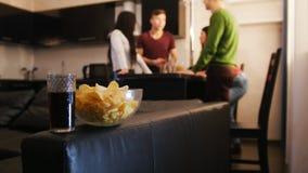 花费时间的年轻朋友公司一起站立在厨房上 碗充满在前景的芯片 股票录像