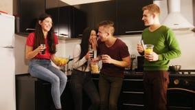 花费时间的年轻朋友公司一起站立在厨房上 谈话和笑 股票录像