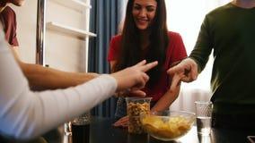 花费时间的年轻朋友公司一起站立在演奏岩石纸剪刀的厨房上 一个少妇 股票录像