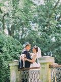 花费时间的快乐的拥抱的新婚佳偶在老阳台上 免版税库存照片