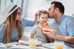 花费时间的愉快的家庭在比萨店 免版税库存图片