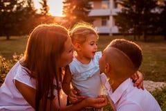 花费时间的愉快的家庭户外走在公园 拥抱一点小孩女孩的母亲和她的儿子 日母亲s 免版税库存图片