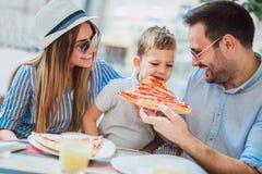 花费时间的愉快的家庭画象在比萨店 免版税库存照片