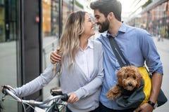 花费时间的愉快的年轻夫妇与狗和自行车一起 免版税库存图片