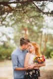 花费时间的愉快的年轻夫妇室外在秋天公园 人给了花有红色头发的一个美丽的女孩 库存图片