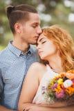 花费时间的愉快的年轻夫妇室外在秋天公园 人给了花有红色头发的一个美丽的女孩 免版税库存图片