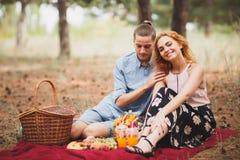 花费时间的愉快的年轻夫妇室外在秋天公园 人给了花有红色头发的一个美丽的女孩 免版税库存照片