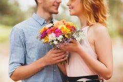 花费时间的愉快的年轻夫妇室外在秋天公园 人给了花有红色头发的一个美丽的女孩 库存照片