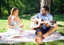 花费时间的愉快的年轻家庭室外在一个夏日 免版税库存照片