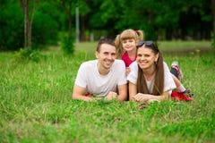 花费时间的愉快的年轻家庭室外在夏日 幸福和和谐在家庭生活中 免版税图库摄影