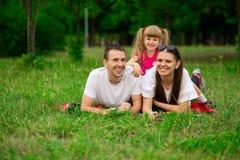 花费时间的愉快的年轻家庭室外在夏日 免版税库存照片