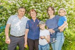 花费时间的愉快的famHappy家庭户外在一个晴朗的夏日 妈妈、爸爸、祖母和两个男孩 免版税库存图片