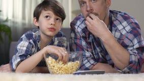 花费时间的男性公司一起看电视和吃玉米花,父权 股票视频
