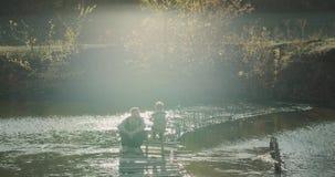 花费有他的爸爸的一个完美的日子儿子在湖边钓鱼和休闲同样时刻 射击在红色史诗 4K 股票视频