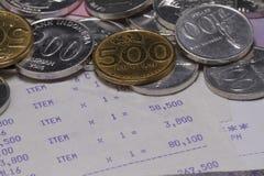 花费金钱和付款说明与硬币、钞票和收据纸在关闭 免版税库存图片