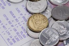 花费金钱和付款说明与硬币、钞票和收据纸 免版税库存图片