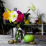 花静物画在花瓶、郁金香的构成和黄水仙的与苹果计算机 免版税库存照片