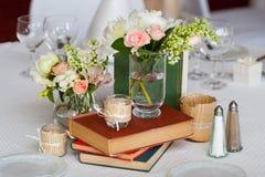 花静物画在玻璃和旧书的在厨房用桌上 免版税库存照片