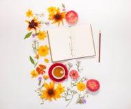 花,一个杯子用清凉茶,在白色背景的一个笔记本 库存照片