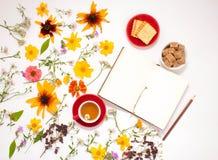 花,一个杯子用清凉茶,在白色背景的一个笔记本 免版税库存图片