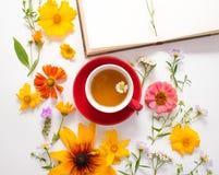 花,一个杯子用清凉茶,在白色背景的一个笔记本 免版税图库摄影