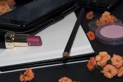 花,智能手机,键盘,在黑背景的笔记本 顶视图 软的妇女企业样式 化妆用品 女性运转的书桌 免版税库存照片