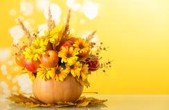 花,水果和蔬菜原始的秋天花束,装饰用小尖峰和脊椎,在南瓜,在黄色 库存照片