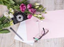 花,葡萄酒照相机,耳机,笔,玻璃顶视图和 免版税库存照片
