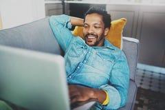 花费在沙发和使用的微笑的有胡子的非洲人数字式片剂的业余时间在现代家 青年人的概念 库存照片