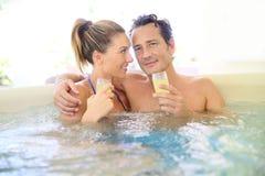 花费好在极可意浴缸的浪漫夫妇时间饮用的香槟 免版税库存图片